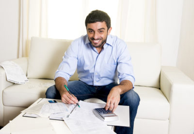 attractive successful latin american man wearing blue shirt and jeans sitting on couch at home doing paperwork, paying bills , accounting and calculating living costs and business benefits and budget with calculator and credit card on the table